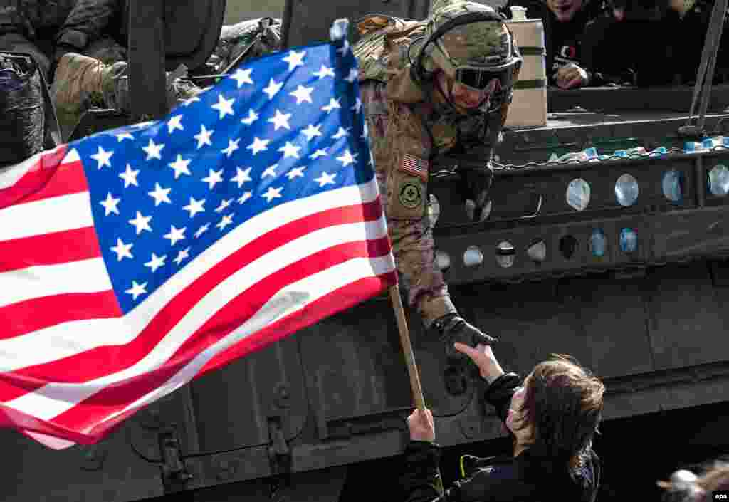 "A woman waves a U.S. flag as she welcomes a soldier of the convoy known as the ""Dragoon Ride."""