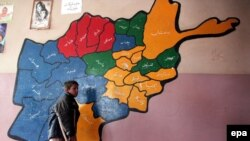 Afghanistan -- A nine-year old orphan walks past a map of Afghanistan drawn on a wall at an orphanage in Kabul, 20Nov2009