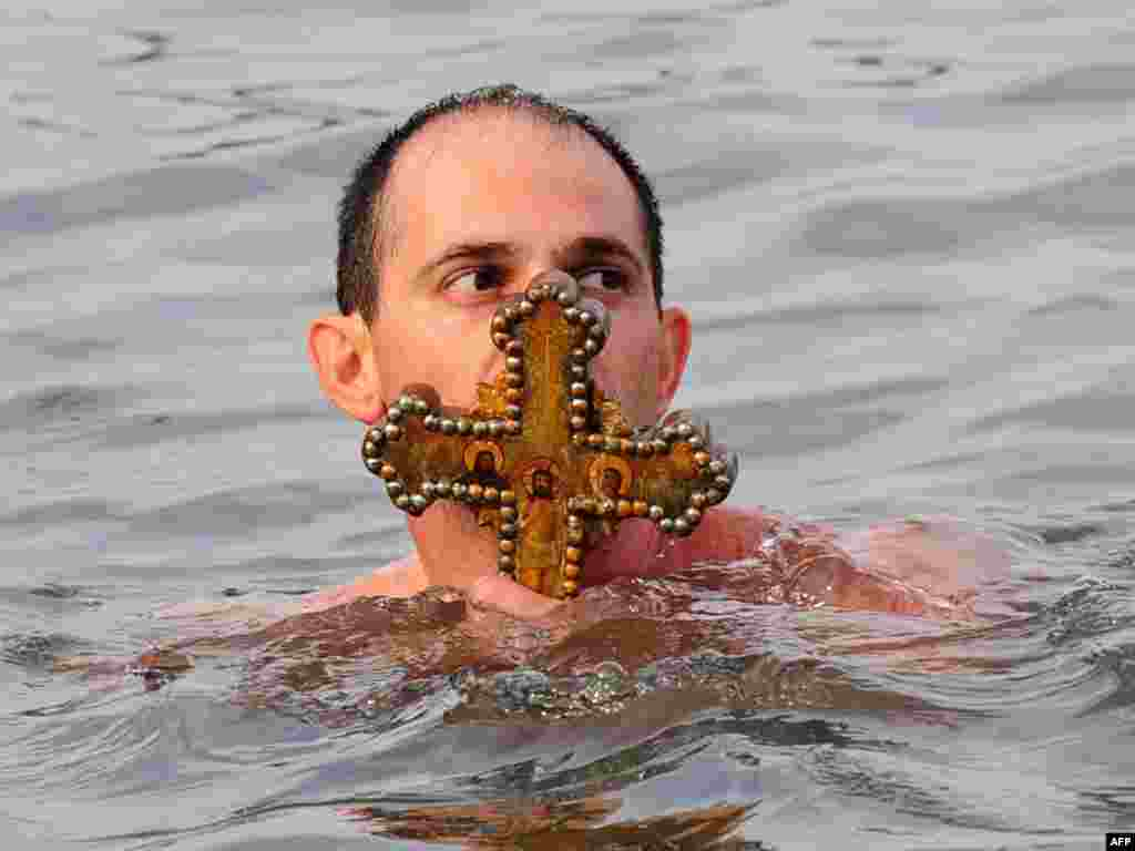 A believer in Turkey kisses a wooden cross thrown into the water by Orthodox Patriarch Bartholomew. - Some Orthodox Christians in Turkey took part in Epiphany Day celebrations on January 6 by jumping into the Bosphorus to retrieve a cross cast into the water by a priest.