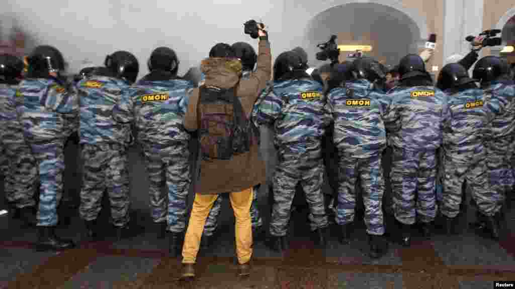 OCTOBER 31, 2012 -- A photographer takes pictures of Interior Ministry officers during a protest rally to defend Article 31 of the Russian Constitution, which guarantees the right of assembly, in St. Petersburg. (Reuters/Alexander Demianchuk)