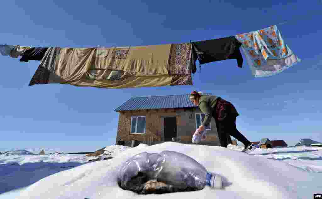 A woman does her laundry in front of her house in Ak-Ordo, a district on the outskirts of the Kyrgyz capital, Bishkek. (AFP/Vyacheslav Oseledko)