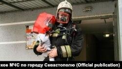 Пожежник виносить дитину з дому, де виникла пожежа, 7 жовтня 2020 року