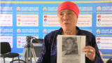 Nauatkhan Jakyp with a picture of her son, Zheniskhan, whom she hasn't seen in more than two years.