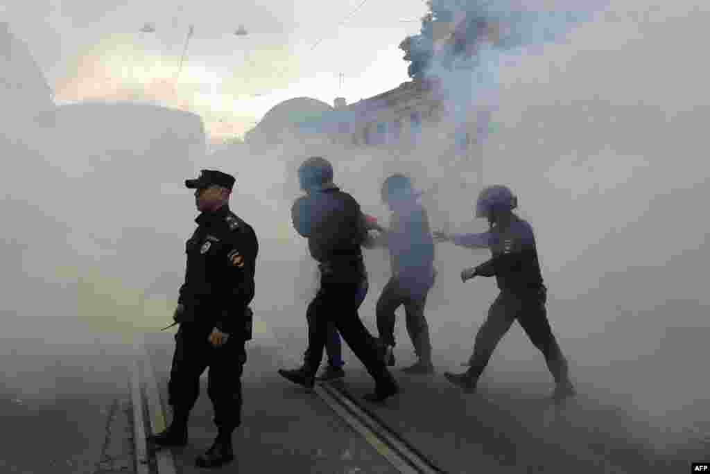 A protester is led away through clouds of smoke in St. Petersburg.
