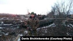 Денис Шинкоренко стоїть біля танка на сході України