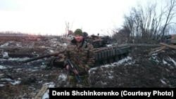 Denis Shchinkorenko stands beside a tank in eastern Ukraine.