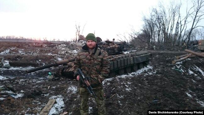 Денис Щинкоренко на фоне танка на востоке Украины