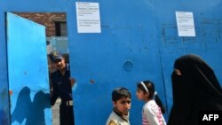 Женщина беседует с охранником возле закрытой христианской миссионерской школы в Лахоре. 11 марта 2013 года.