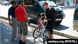 Алматы көшесінде велосипед теуіп жүрген тұрғын. 2 маусым. 2012 жыл.