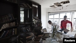 People clean up debris in an apartment damaged after a rocket, fired from Gaza, landed in the southern city of Kiryat Malachi on November 15.