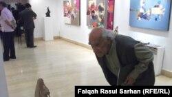 الفنان الراحل محمد غني حكمت ينظر الى عمل نحتي في معرض بعمّان