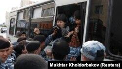 Сотрудники спецподразделения полиции заталкивают женщину в автозак. Во время задержаний предполагаемых участников несанкционированной акции протеста в ряде городов, по данным МВД, были задержаны «около 100 человек». Алматы, 21 сентября 2019 года.