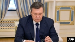 Viktor Yanukovych looks down at his glasses before signing an agreement in Kiev on February 21 to end the country's worst crisis since independence.