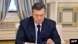 Ukraine - Ukrainian President Viktor Yanukovych looks down at his glasses before signing an agreement in Kiev on February 21, 2014 to end the splintered country's worst crisis