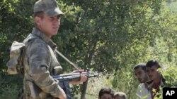 Турецкий военный и беженцы из Сирии