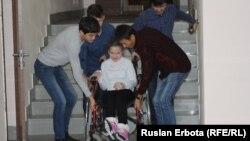Молодые люди спускают девушку в инвалидной коляске вниз по ступеням лестницы. Астана, 18 ноября 2015 года.