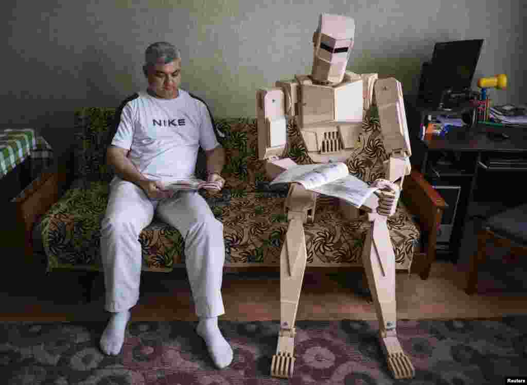 Ukraine's Dmitry Balandin poses with his wooden model called Cylon in his flat in Zaporizhzhya. It took Balandin six months to build the model from 500 parts. Balandin says he does not use blueprints and designs the parts as he works on them. He says he would love to build metal models but that it is impossible to do so in his small apartment. He plays with Cylon as a child would play with a doll and is now making a girlfriend for his model. (Reuters/Gleb Garanich)