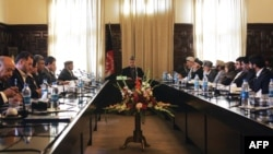 Which other ministers might Afghan President Hamid Karzai (center, presiding over a cabinet meeting) be forced to sacrifice?