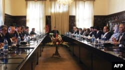 A new Afghan cabinet was being sworn in on January 18 as explosives-bearing militants were attacking just a kilometer or so away.