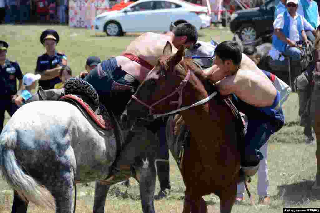 Момент поединка борцов на лошадях.
