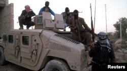 Sunni gunmen sit on top of an Iraqi Army vehicle left by Iraqi soldiers during clashes in the city of Fallujah on January 9.