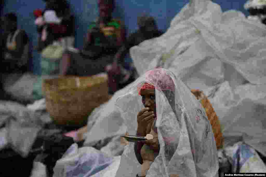 A woman protects herself from rain brought by Hurricane Irma as she eats lunch in a street of Cap-Haitien, Haiti, on September 7. (Reuters/Andres Martinez Casares)
