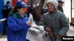 Украина - Женщина раздает бесплатную газету с заголовком на первой полосе «Крым выбрал Россию», Симферополь, 17 марта 2014 г.