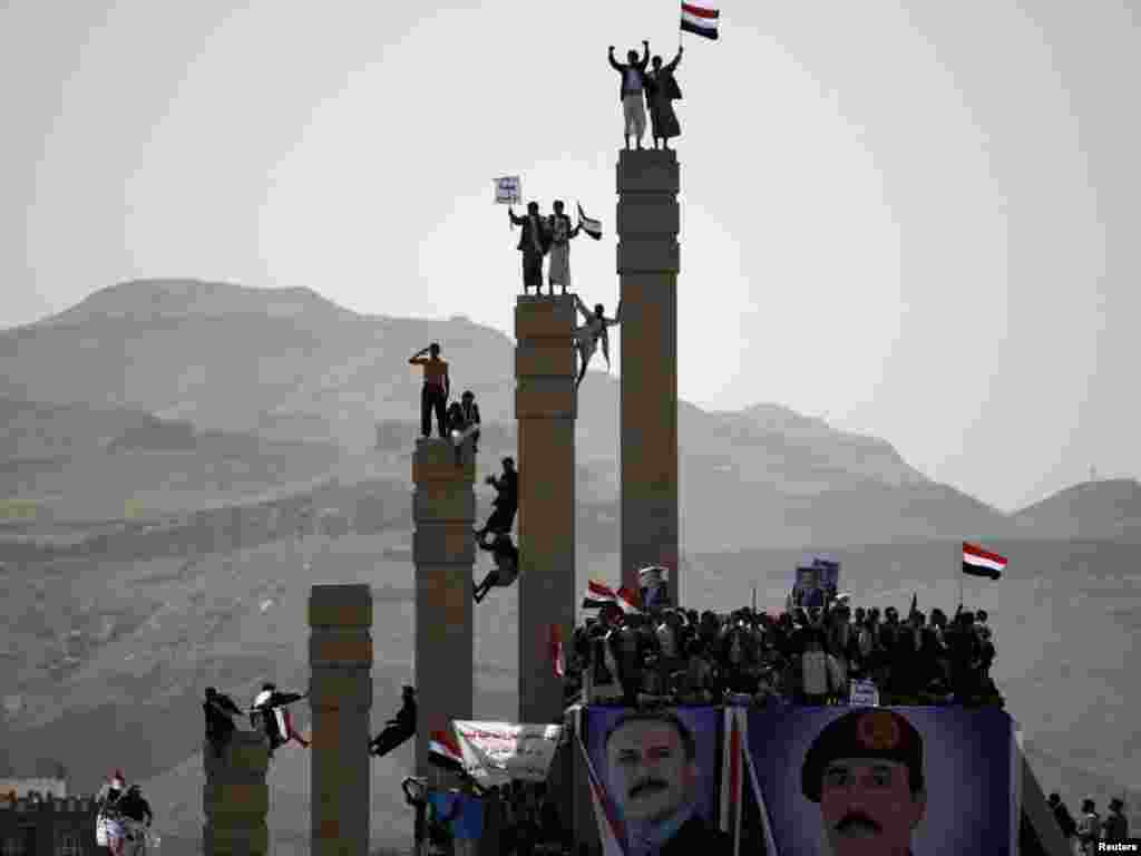 Supporters of Yemen's President Ali Abdullah Saleh stand on pillars during a rally to show their support in Sanaa on April 1. Embattled Saleh told a huge rally of supporters that he would sacrifice everything for his country, suggesting he has no plans to step down yet. Photo by Khaled Abdullah for Reuters