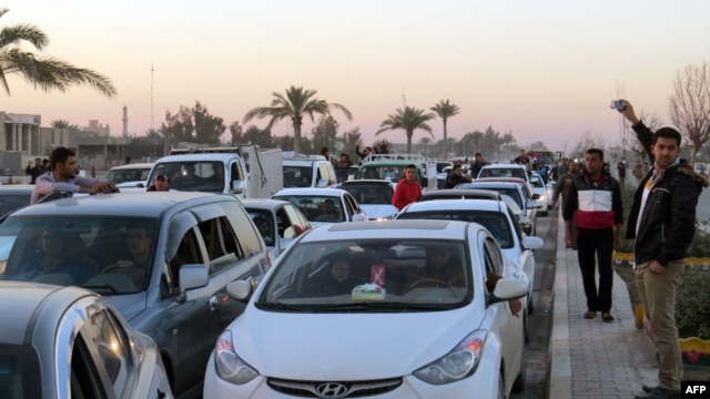 Iraqis drive their vehicles early on December 29 through the city of Ramadi, the capital of Iraq's Anbar Province, after Iraqi forces recaptured the city from Islamic State.