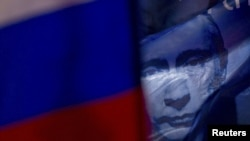 A Russian flag decorated with a portrait of Vladimir Putin flies during a pro-Putin rally in central Moscow.