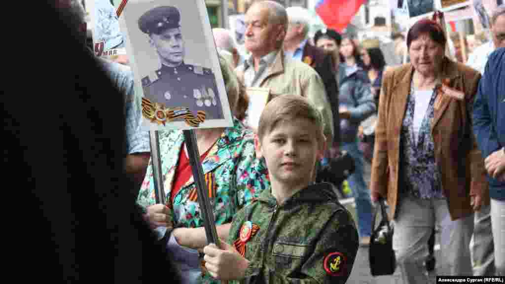 """9 mayıs 2018, Aqyar. Arbiy kiyimli oğlan """"Ölmez polk"""" aktsiyası vaqtında asker süretinen"""
