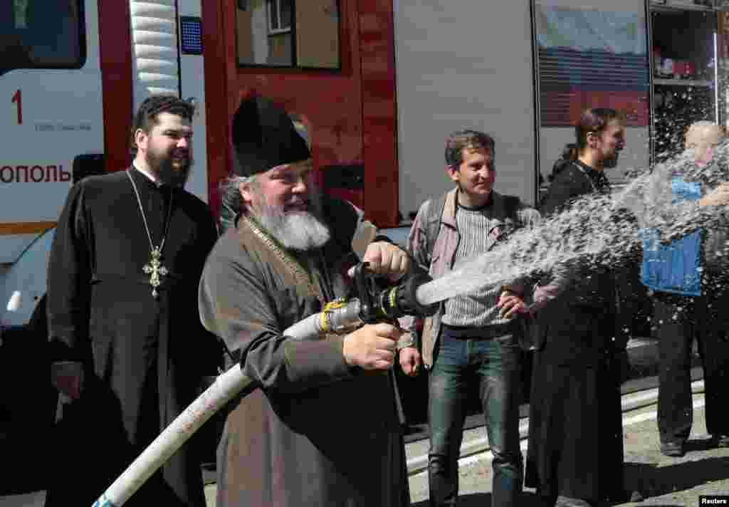 An Orthodox priest takes part in practical exercises on fire-extinguishing in Simferopol, Crimea, illegally annexed by Russia in 2014. (Reuters/Pavel Rebrov)
