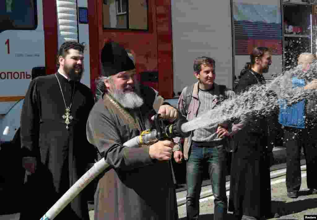 Священнослужителі відпрацьовують навички гасіння пожежі під час навчань МНС у Сімферополі, 4 квітня 2017 року