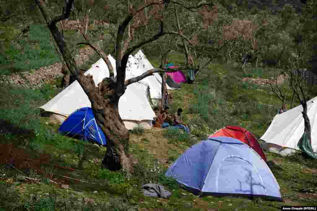 Мужчины из Пакистана рядом с палаткой в созданном волонтерами лагере для беженцев близ села Мориа на Лесбосе.
