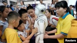 Дүйнөлүк робот конференциясында балдар робот менен ойноодо. Бээжин, 17-август, 2018-жыл.