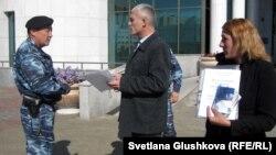 Сотрудник полиции просит гражданского активиста Руслана Оздоева покинуть территорию сената парламента. Астана, 24 сентября 2012 года.