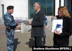 Сотрудник полиции просит гражданского активиста Руслана Оздоева (в центре) покинуть территорию у входа в парламент. Астана, 24 сентября 2012 года.