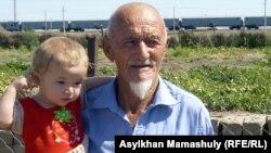 Мантай-аксакал, имам мечети села Кейден, с внучкой.