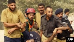 Pakistani policemen remove an injured colleague from a training center after gunmen attacked in Lahore.