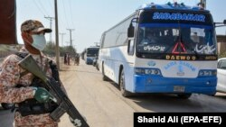 A soldier stands guard as buses carry pilgrims returning from Iran via the Pakistan-Iran border town of Taftan in March.