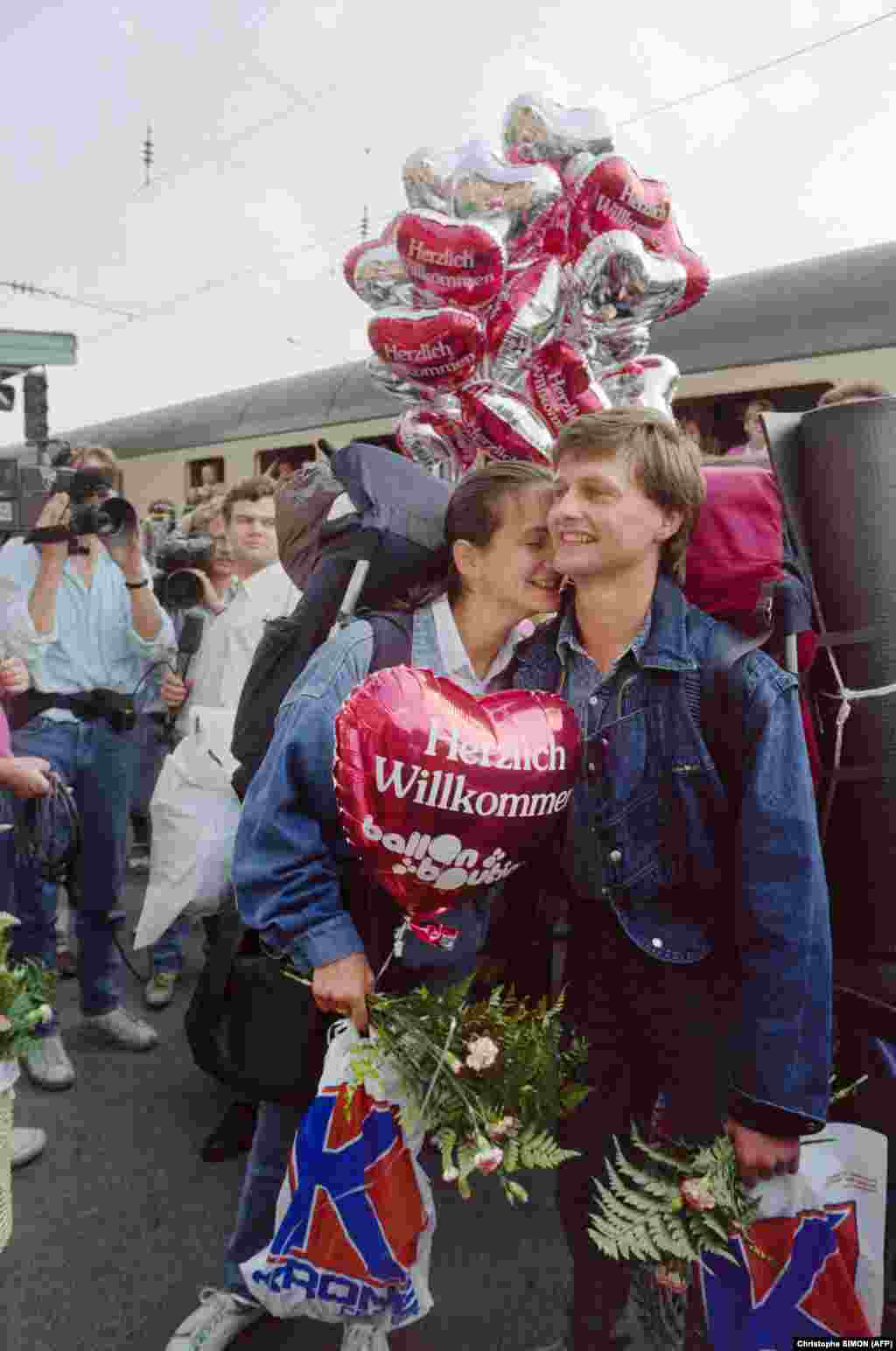 """A smiling couple holds a balloon reading """"Warm Welcome"""" in Passau, Germany, after riding by train from Lake Balaton, Hungary."""