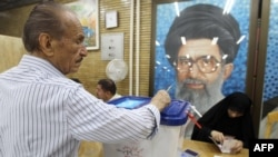 An Iranian casts his ballot in Tehran for elections in 2012 in front of a portrait of Supreme Leader Ayatollah Ali Khamenei.