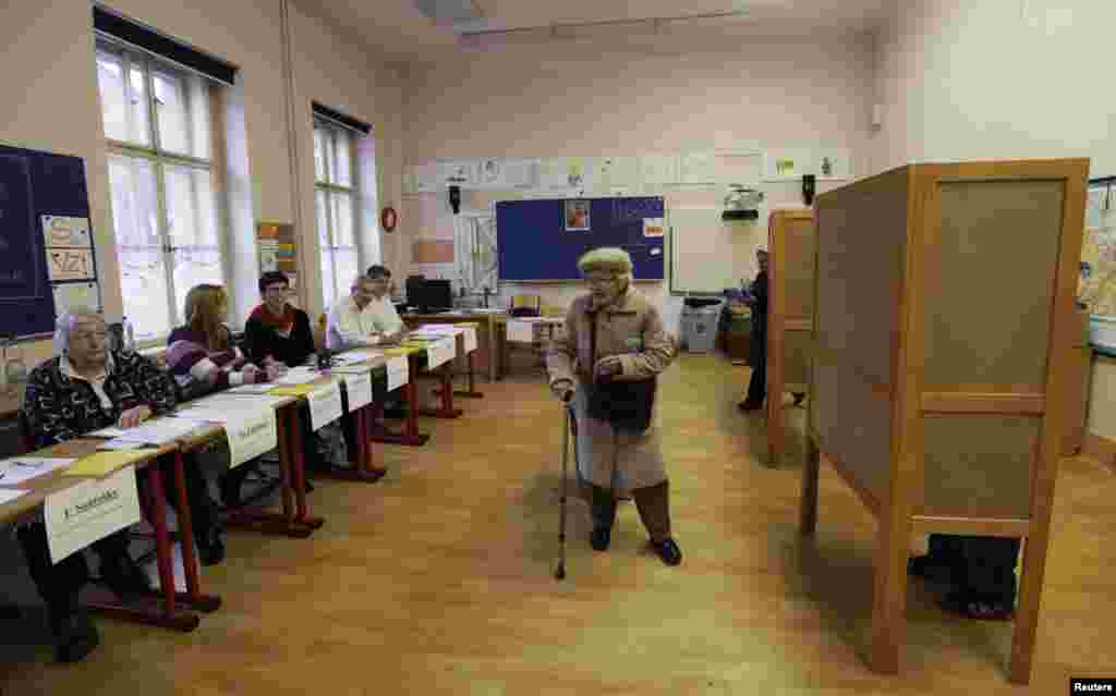 An elderly woman leaves a polling station in Prague.