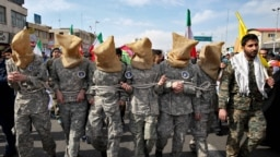 Members of Iranian Basij paramilitary force reenact the January capture of U.S sailors by the Revolutionary Guards in the Persian Gulf, in a rally commemorating the 37th anniversary of Islamic Revolution in Tehran, Feb. 11, 2016.