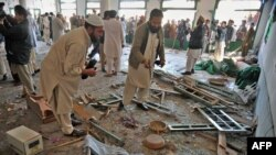 Security personnel investigate the bomb blast site in Nowshera