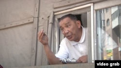 Үйін іштен жауып алған Әділбек Мейрамов егер үйге сот орындаушылары жақындаса, газ баллонын жарып жіберетінін ескертіп тұр. Астана, 24 маусым 2016 жыл.
