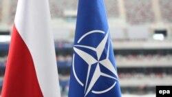 Флаг Польши и флаг НАТО перед Национальным стадионом в Варшаве, где проходит саммит. 8 июля