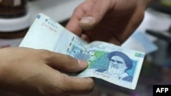 A woman pays with a 20,000-rial banknote in a grocery store in Tehran.