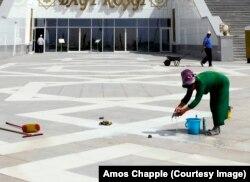 Женщина моет плитку на проходе перед Дворцом бракосочетаний в столице.