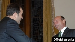 "Moldova's Vlad Filat (left) greets Romania's Traian Basescu -- ""Are we speaking Moldovan or Romanian?"""